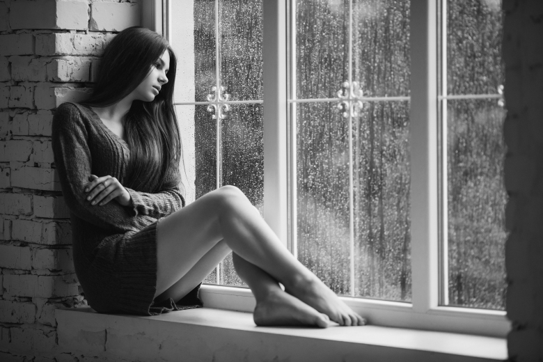 Beautiful young woman sitting alone close to window with rain dr