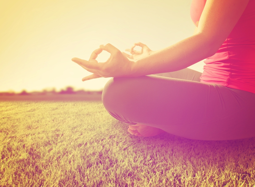 hands of a woman meditating in a yoga pose on the grass toned w