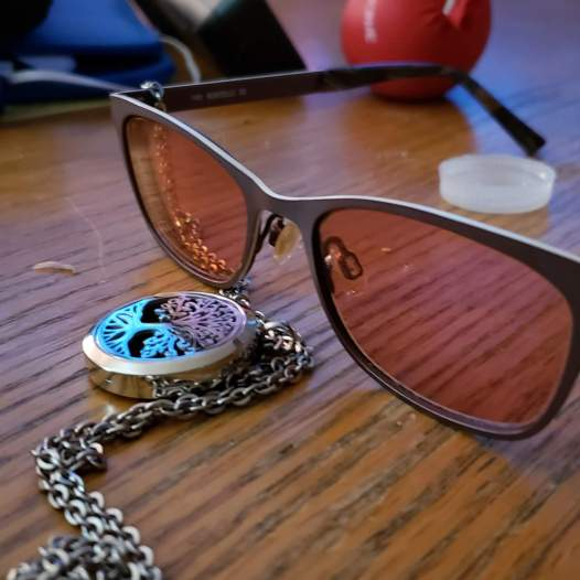 Tinted migraine glasses and essential oil necklace